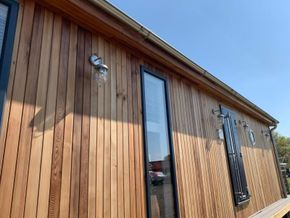 Cedar clad with marine detail lighting and galvanised guttering
