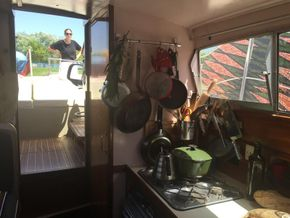 Interior of cabin, kitchen and stove, looking out from v-berth