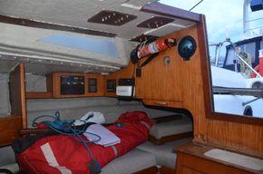Bag of sails on single bed next to entrance hatch. Navman VHF radio
