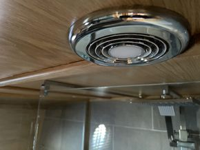 Bathroom extractor fan with integrated downlight
